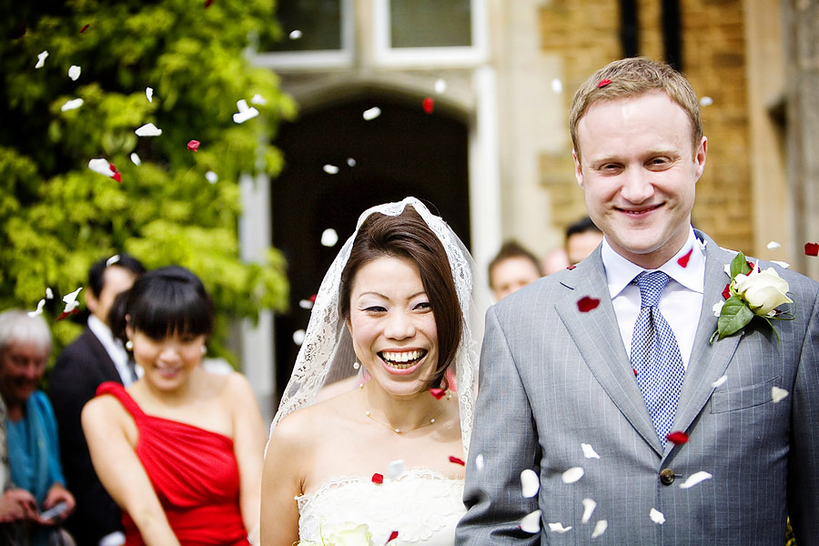 Cofetti being thrown at the wedding couple at Hartsfield Manor in Surrey
